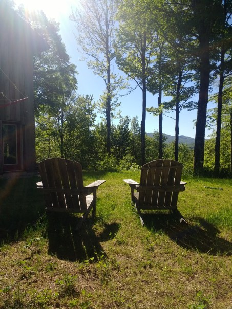 Two Adirondack chairs in the summer sun.