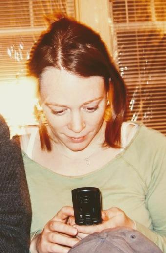 Woman looks as flip phone screen.